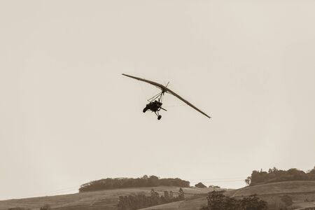 piste atterissage: Flying microlight aircraft plane pilot passenger landing on rural countryside farm grass airstrip