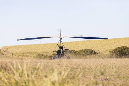 piste atterissage: Flying microlight  plane pilot landing on rural countryside grass airstrip