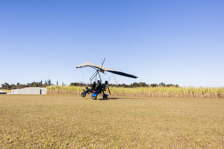 airstrip: Flying microlight aircrafts flying pilot passenger take off and landing on rural countryside farm grass airstrip