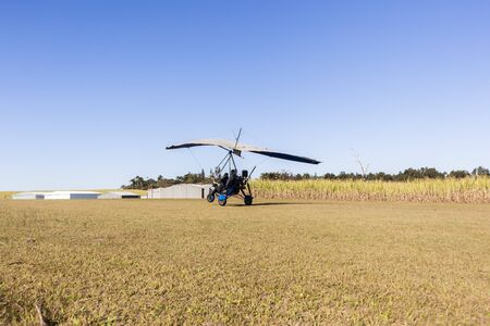 rural countryside: Flying microlight aircrafts flying pilot passenger take off and landing on rural countryside farm grass airstrip