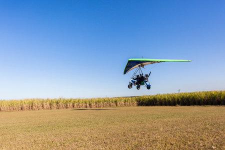 campagne rural: Voler en ULM pilote d'avion passager atterrissage sur piste en herbe paysage rural Editeur