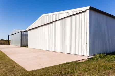 Metal warehouse hangars rural countryside grass airstrip