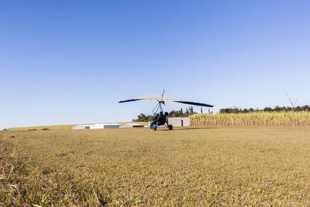 airstrip: Flying microlight plane pilot passenger landing on rural countryside grass airstrip