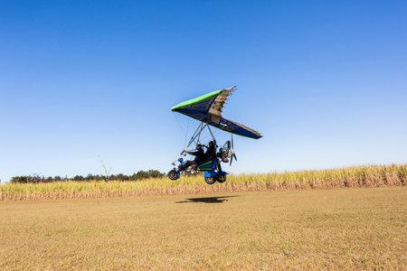 airstrip: Flying microlight plane pilot passenger  landing on rural countryside grass airstrip Editorial