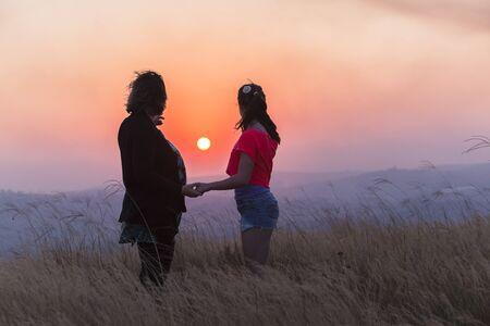 madre e hija adolescente: Madre adolescente relación hija viendo el sol va hacia abajo sobre el paisaje en día final.