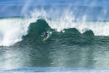 swells: Surfing surfer escape getting hit by ocean wave water power Stock Photo