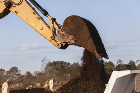 Construction earthworks excavator machine closeup bucket bin loading truck. Stock Photo