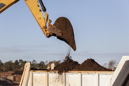 loading truck: Construction earthworks excavator machine closeup bucket bin loading truck. Stock Photo