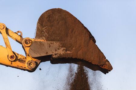 soil: Construction earthworks excavator machine bucket bin closeup loading truck. Stock Photo