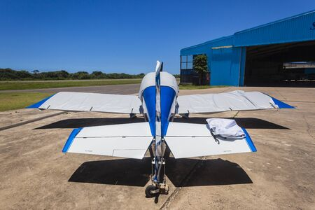 prop: Aircraft small single prop plane covered outside hangar airstrip