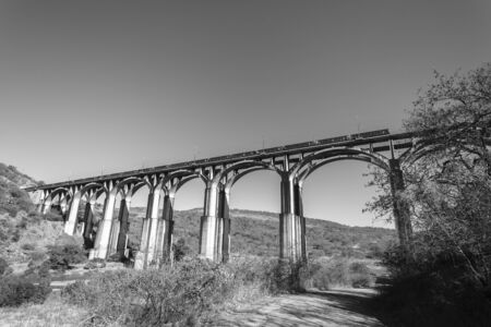arched: Train crossing tall high arched concrete railway line bridge over valley river rugged landscape vintage black and white.