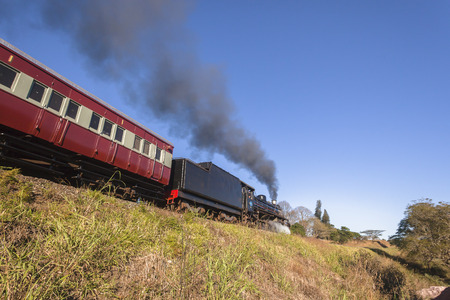 kz: Steam train with passenger coaches and tourists departs Kloof station and powers its way towards Inchanga Valley of Thousand hills outside Durban KZ Natal South Africa.