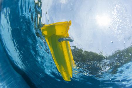 Swimming pool underwater girl floating relaxing floating on yellow air matt li lo  home solitude. Stock Photo