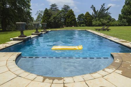 Swimming pool blue water yellow air matt li lo home solitude. Stock Photo