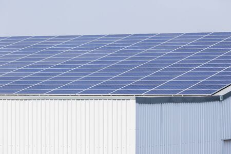 power of savings: Solar panel screens cover building rooftops for clean energy power savings from sunlight
