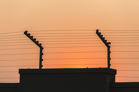 deterent: Electrified  security wire high voltage fencing on wall at sunset