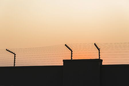 deterent: Electrified security wire high voltage fencing on wall at sunset Stock Photo