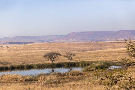 waterhole: Waterhole dry season fields trees rural farming mountain landscape Stock Photo