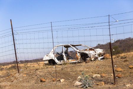 crashed: Crashed Car  wreck destroyed stripped vehicle body behind electrical fence Stock Photo