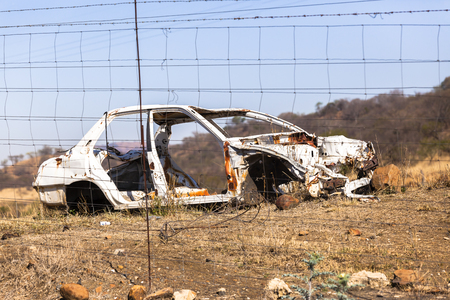 stripped: Crashed Car  wreck destroyed stripped vehicle body behind electrical fence Stock Photo