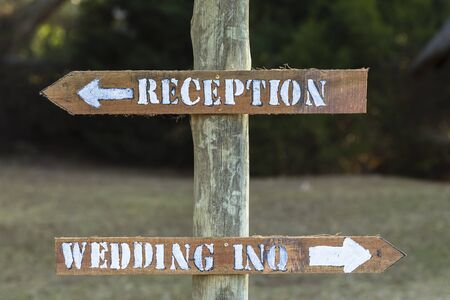 inquiries: Signs wedding inquiries reception outside rural countryside wood pole materials.