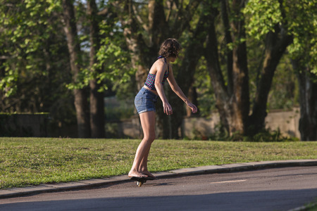 driveway: Girl riding snake skate board on home driveway late afternoon