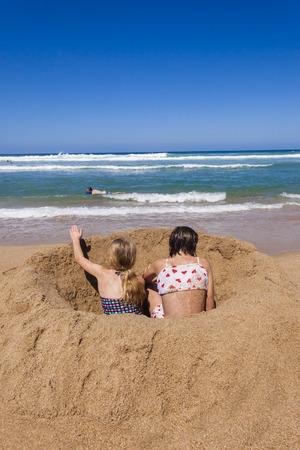 shorebreak: Sisters girls sitting beach sands ocean wave shorebreak wash holidays