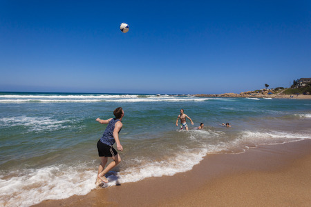 playtime: Teenagers girls boys football playtime on beach ocean water shoreline holiday landscape Stock Photo