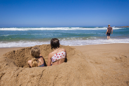 shorebreak: Sisters girls sitting beach sands ocean wave shorebreak  dad washes holidays
