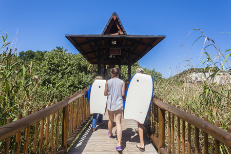33f9e3cdd83 Teenagers girls boys walking across river wooden bridge towards beach  holiday landscape Stock Photo
