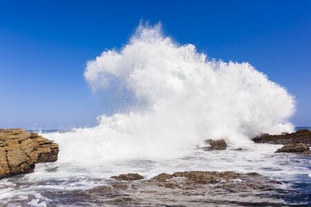 crashing: Ocean wave crashing rocky coastline exploding white water power