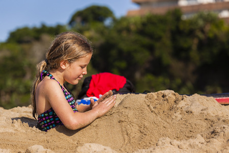 playtime: Young girl playing beach sands.
