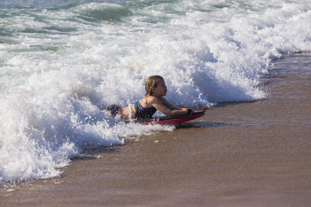 onto: Young girl surfing rides ocean wave onto beach sands.