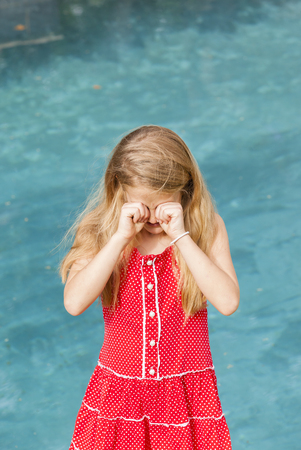 hand rubbing: Young girl red dress blue pool rubbing eyes both hands action vertical photo.