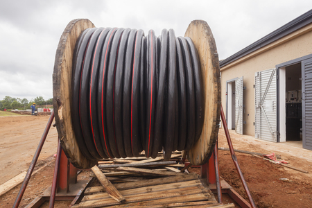 sub station: Large new electrical cable roll high voltage outside new sub station for installation.