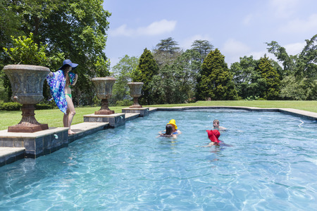 cool off: Family teenagers girls red yellow blue hats boy summer cool off swimming pool