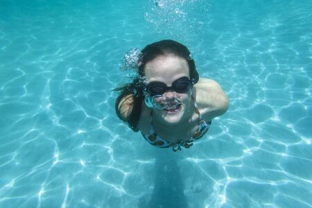 girl underwater: Teen girl underwater swimming pool summer fun portrait.
