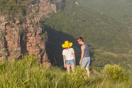 Teenagers girl boy hiking wilderness overlooking valley rocky cliffs landscape.