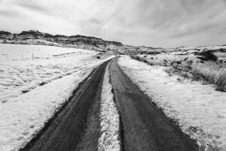 mud snow: Mountains Snow dirt road mud tracks towards hilltop in vintage black and white landscape