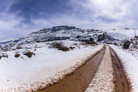 rugged terrain: Mountains Snow dirt road mud tracks landscape Stock Photo