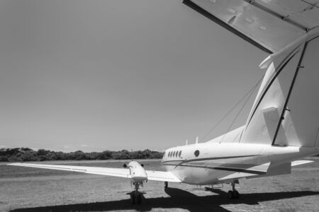 twin engine: Plane twin engine propeller aircraft parked midday airport vintage black and white.