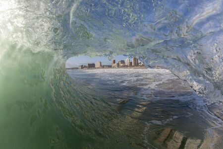 swells: Wave ocean swimming inside tube of water crashing breaking beauty nature power.
