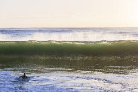 crashing: Wave ocean wall crashing front of  surfer paddling. Stock Photo