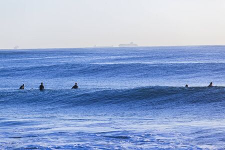 swells: Waves  ocean with surfers waiting back line.