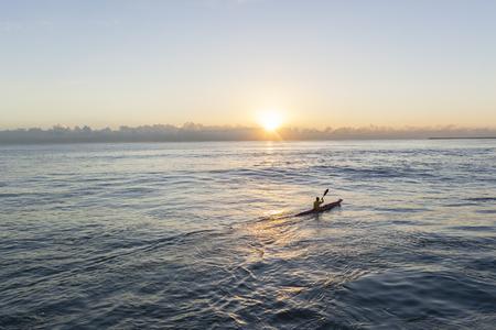 Vaarder surf ski kano water van de oceaan zonsopgang training.