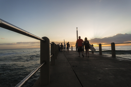 surfers: Dawn sunrise beach pier ocean sunrise surfers surfing public activity. Stock Photo