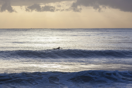 silhouetted: Surfer in ocean waves silhouetted morning sunrise surfing session. Stock Photo