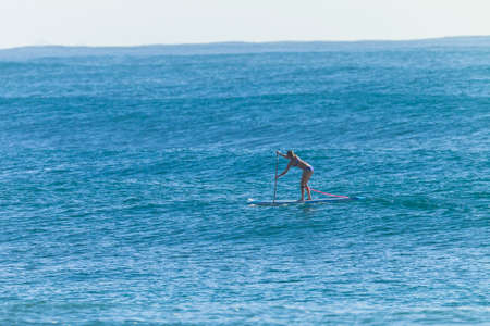 swells: Girl athlete paddling sup board on ocean wave swells. Stock Photo