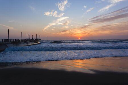 ocean waves: Beach Pier ocean waves sunrise color reflections shoreline skyline landscape Stock Photo
