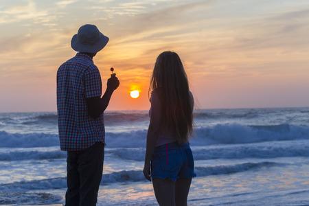 silhouetted: Friends man girl silhouetted talking watching beach ocean sunrise li